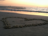 Beach sunset with heart in the sand